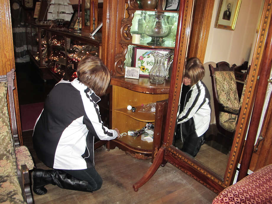 In this April 15, 2016 photo, docent Kathryn Woodlock looks inside a cabinet whose doors have seemingly opened on their own at the Palmyra, N.Y., Historic Museum. The museum is one of nearly 70 stops along New York's Haunted History Trail, which maps out places where there have been claims of paranormal activity and invites tourists to see for themselves. (AP Photo/Carolyn Thompson) ORG XMIT: NYR402 Photo: Carolyn Thompson / Copyright 2016 The Associated Press. All rights reserved. This m