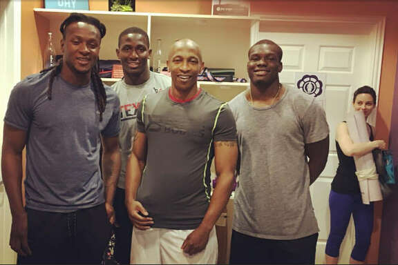 Texans players (from left) DeAndre Hopkins, Alfred Blue, Keith Mumphery and running backs coach Charles London (center) did some yoga at a Houston studio Thursday.