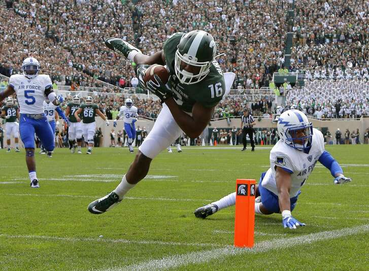Michigan State's Aaron Burbridge (16) comes down with a 28-yard reception for a touchdown against Air Force's Kalon Baker, right, and Dexter Walker (5) during the second quarter of an NCAA college football game, Saturday, Sept. 19, 2015, in East Lansing, Mich. Michigan State won 35-21.  (AP Photo/Al Goldis)