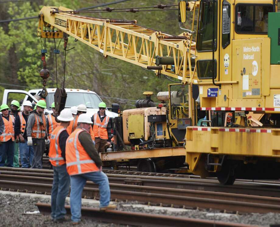 MTA employees gather after a piece of construction equipment derailed between the Greenwich and Cos Cob train stations in Greenwich, May 5, 2016. The derailment occured shortly after noon, causing a minor injury to one worker and delays on the New Haven line. Photo: Tyler Sizemore / Hearst Connecticut Media / Greenwich Time