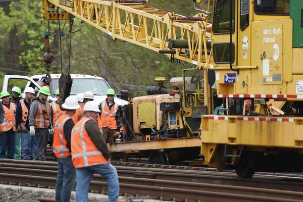 MTA employees gather after a piece of construction equipment derailed between the Greenwich and Cos Cob train stations in Greenwich, May 5, 2016. The derailment occured shortly after noon, causing a minor injury to one worker and delays on the New Haven line.
