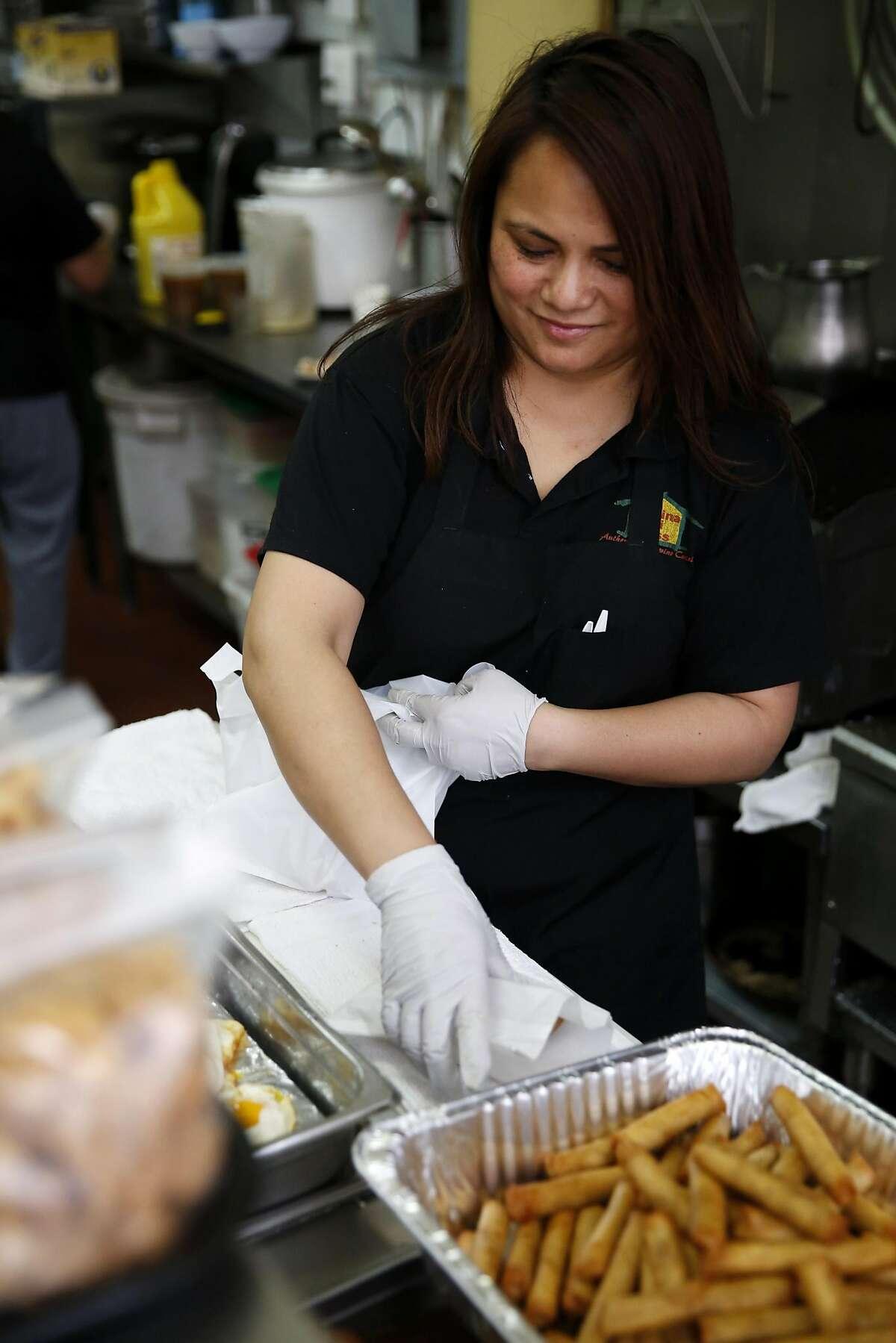 Maria San Antonio puts together a lunch order for a customer at Kusina Ni Tess in San Francisco, California, on Thursday, May 5, 2016.