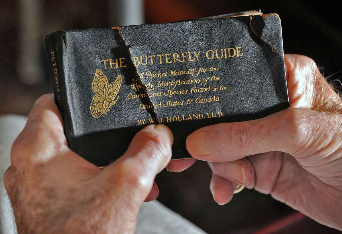 Warren Rymiller holds a Butterfly guide from 1916 at his home Thursday March 3, 2016 in Brunswick, NY. The book was found in the floorboards of his home during renovations. (John Carl D'Annibale / Times Union)