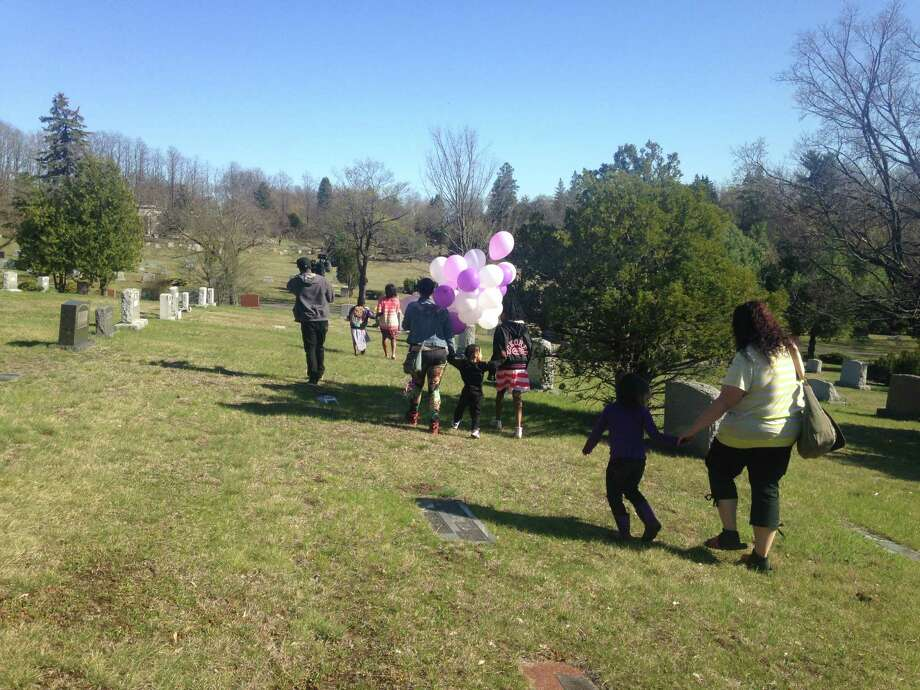 Prince Sprauve, follows Janelle Moore, in striped sweater, and a group of family, friends and strangers to her daughter's grave. (Photo by Amy Biancolli)
