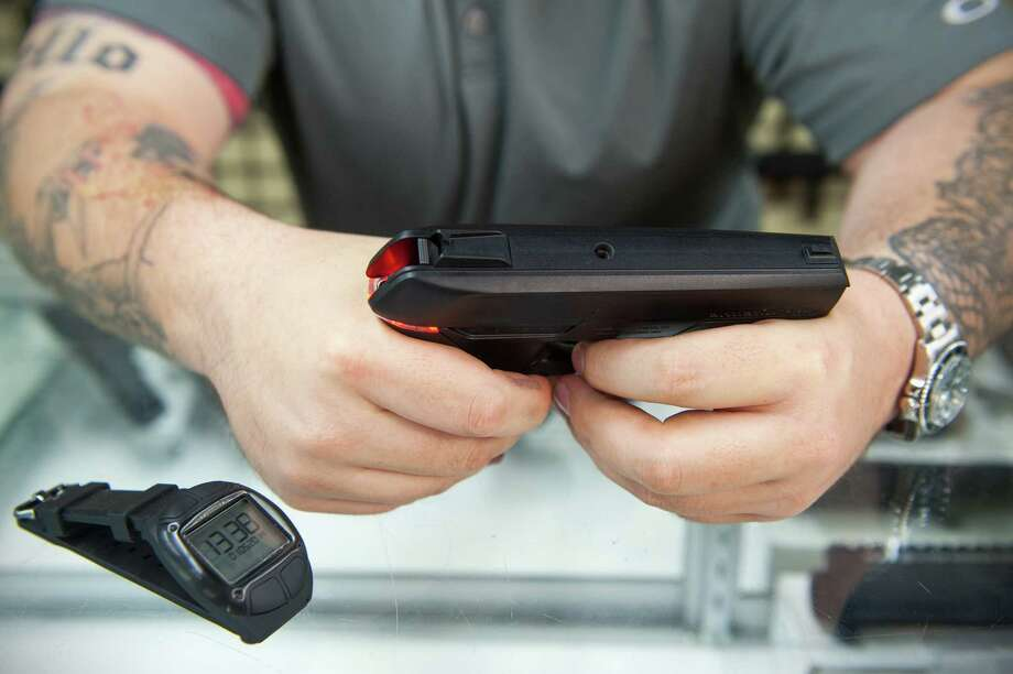 ROCKVILLE, MD - MAY 1: Andy Raymond demonstrates the Armatix iP1, a .22 caliber smart gun that has a safety interlock at Engage Armaments May 1, 2014 in Rockville, MD.  The gun glows red when it is not synced with the watch, blue when the magazine is not engaged and green when it is good to go. (Photo by Katherine Frey/The Washington Post via Getty Images) ORG XMIT: 95654735 Photo: The Washington Post / 2014 The Washington Post