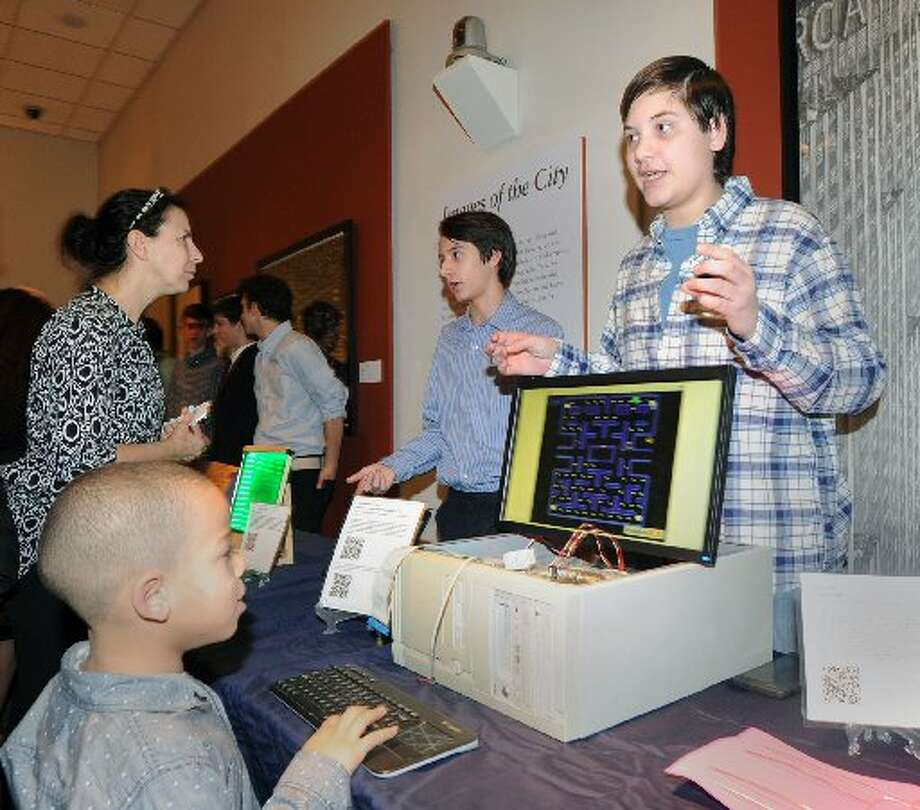 """Greenwich High School sophomore James Bonney, right, explains his computer game """"Modernism Pacman"""" to visitors during a February exhibition at the Bruce Museum of projects created by Greenwich High School sophomores in the Innovation Lab program. A $44,500 grant from the Greenwich Alliance for Education is supporting the Innovation Lab this school year. Photo: Bob Luckey"""