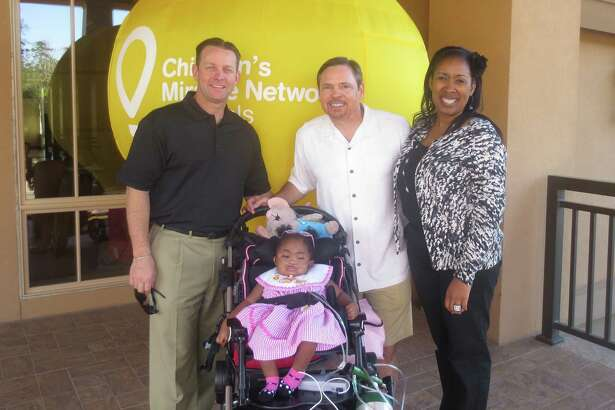 Miracle baby, Aspen, shown with Derek Ellis of Marriott Hotels of Houston, Dean Melton with RE/MAX The Woodlands & Spring, and her mom, Ane, is one of many Children's Miracle Network Hospitals' success stories.