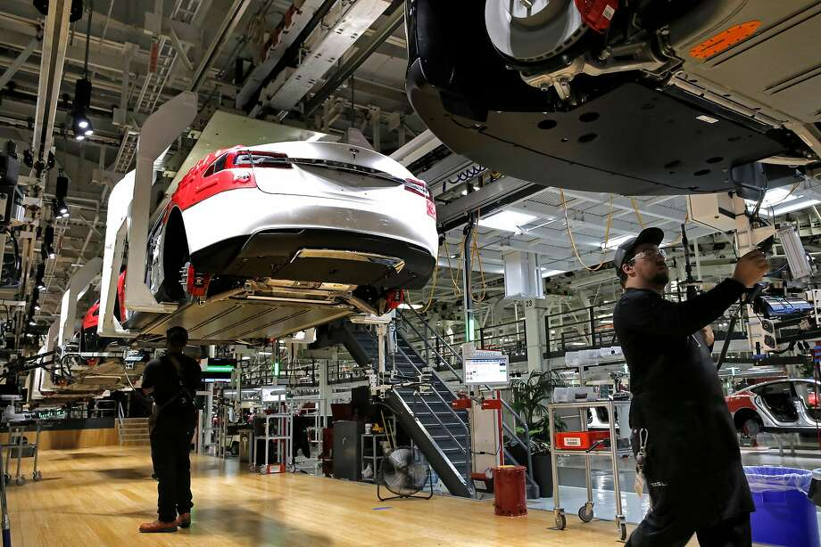 Workers under the electric cars as they move through the assembly line at Tesla Motors, California's only full-scale auto manufacturing plant as seen on Thurs. Feb. 19, 2015,  in Fremont, Calif. Photo: Michael Macor, The Chronicle