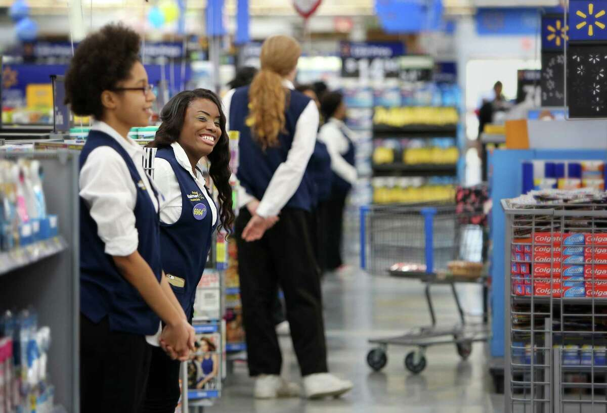 Cashier Sandra Brown, second left, greets customers earlier this year at the Wal-Mart store in Horn Lake, Miss. Wal-Mart founder Sam Walton started the tradition, though four years ago it removed greeters.