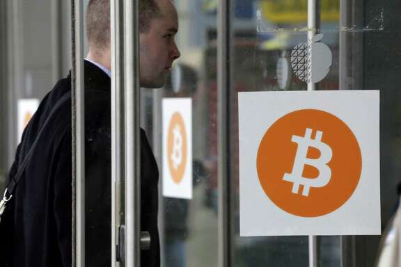 A man enters the Inside Bitcoins conference and trade show, Monday, April 7, 2014 in New York. Bitcoin users exchange cash for digital money using online exchanges, then store it in a computer program that serves as a wallet. The program can transfer payments directly to merchants or individuals around the world, eliminating transaction fees and the need for bank or credit card information. (AP Photo/Mark Lennihan)