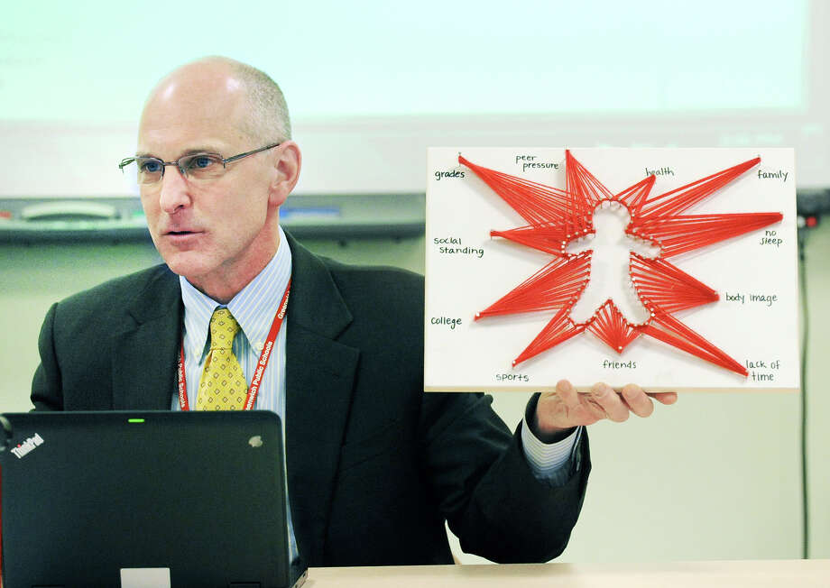 GHS Headmaster Chris Winters holds up a student art work. depicting student stress. Photo: Bob Luckey Jr. / Hearst Connecticut Media / Greenwich Time