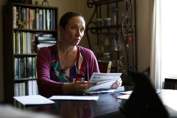 Pascale Leroy looks up at her husband Robert Bell while going through some of their healthcare-related paperwork in their home in San Francisco, California, on Thursday, May 5, 2016.