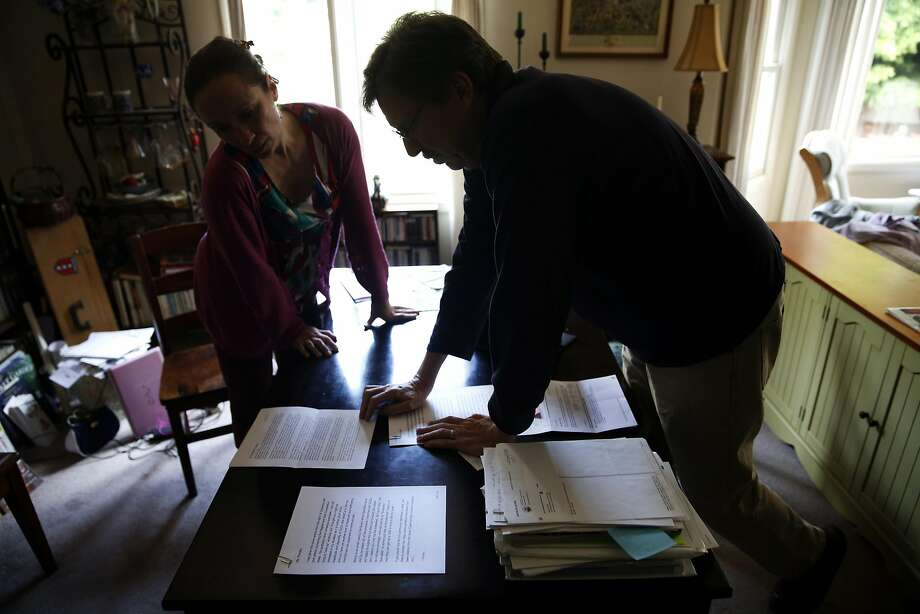 Pascale Leroy (left) and her husband, Robert Bell, go through the pile of paperwork generated by their problem renewing a Covered California policy. Photo: Connor Radnovich, The Chronicle