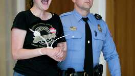 Officer K.A. Thompson escorts a woman arrested at a sit-in at state Rep. Tim Moore's office in Raleigh, N.C. News reports said 54 people protesting the transgender law were arrested.