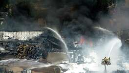 Firefighters battle a four-alarm fire at Custom Packaging and Filling Co. in Houston. The firm apparently handles a variety of hazardous substances, but it was unclear which ones.