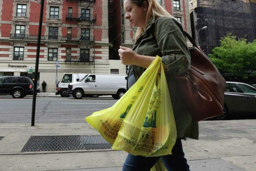 A woman carries her purchase in plastic bags from a Gristedes supermarket on New York's Upper West Side, Thursday, May 5, 2016. Merchants in New York who now hand out billions of free, disposable plastic bags each year to shoppers and diners would have to start charging 5 cents each for the convenient but environmentally unfriendly receptacles under a bill set for a city council vote Thursday. (AP Photo/Richard Drew) ORG XMIT: NYRD103