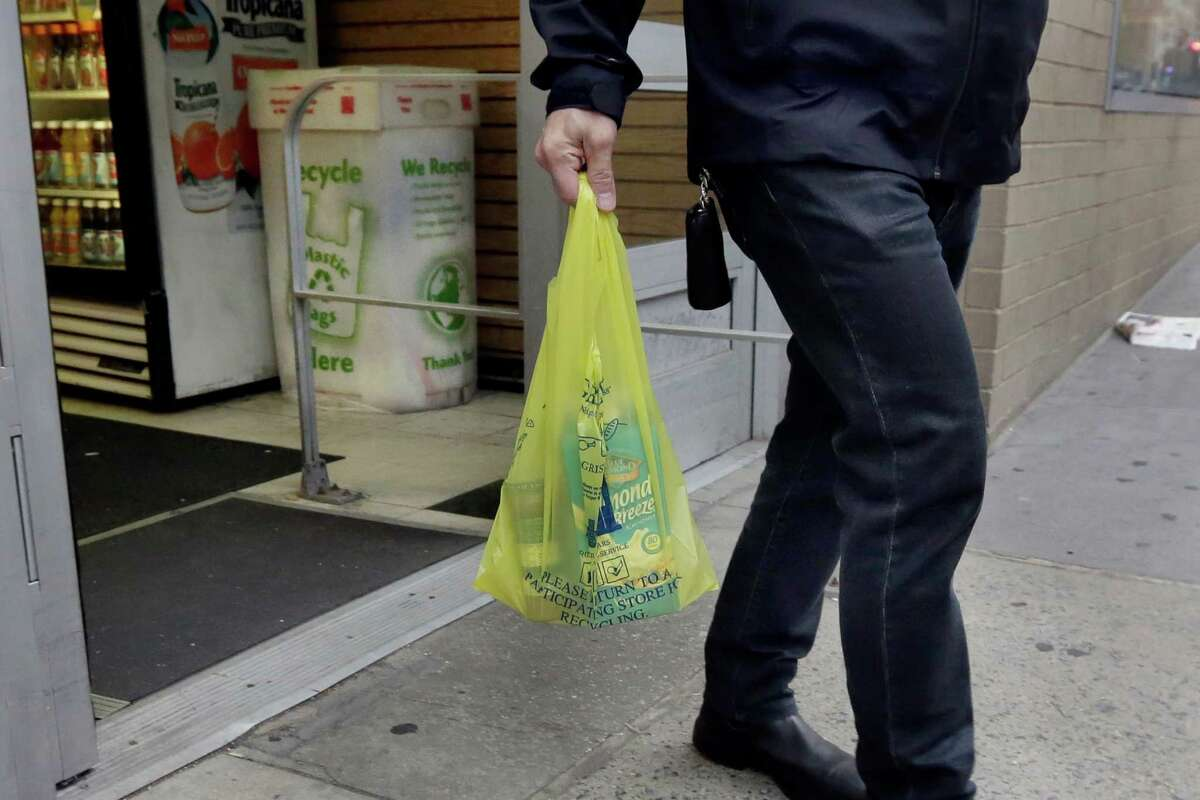 A man carries his purchase in a plastic bag from a Gristedes supermarket on New York's Upper West Side, Thursday, May 5, 2016. Merchants in New York who now hand out billions of free, disposable plastic bags each year to shoppers and diners would have to start charging 5 cents each for the convenient but environmentally unfriendly receptacles under a bill set for a city council vote Thursday. (AP Photo/Richard Drew) ORG XMIT: NYRD101