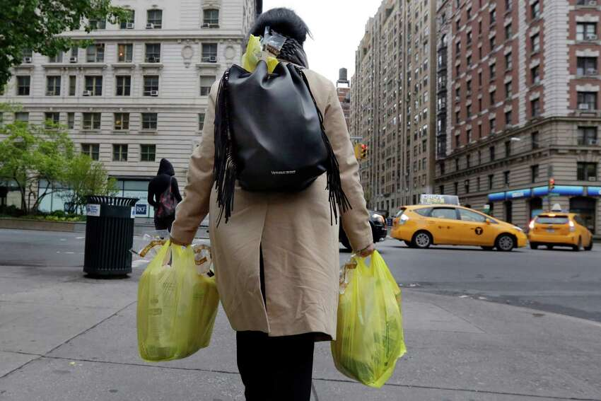 A woman carries her purchase in plastic bags from a Gristedes supermarket on New York's Upper West Side, Thursday, May 5, 2016. Merchants in New York who now hand out billions of free, disposable plastic bags each year to shoppers and diners would have to start charging 5 cents each for the convenient but environmentally unfriendly receptacles under a bill set for a city council vote Thursday. (AP Photo/Richard Drew) ORG XMIT: NYRD102