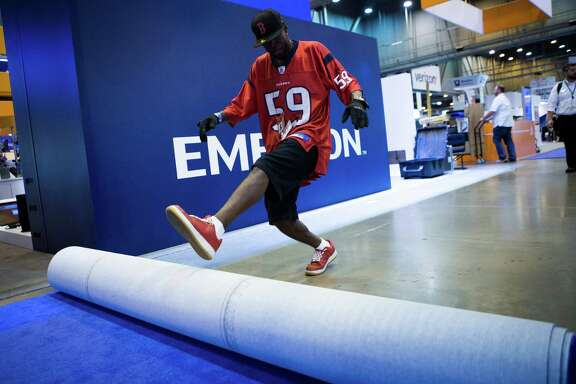 Cornell Jackson rolls up a carpet as part of the breakdown process of the 2016 Offshore Technology Conference on Thursday at NGR Center. Attendance and the energy level at the conference were down from years past.
