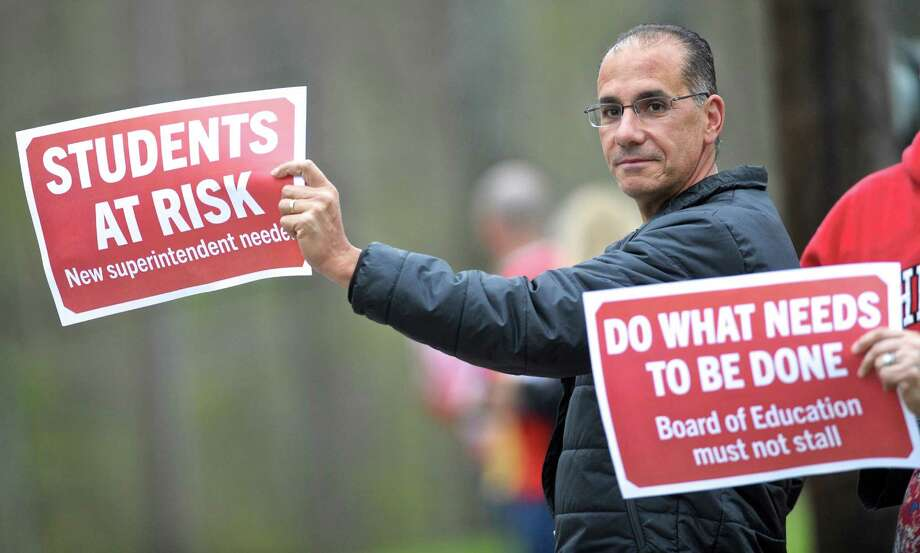 New Fairfield parent Jim Gasparino stands with teachers along the road in front of Meeting House Hill School before the New Fairfield Board of Education meeting on Thursday night. Teachers and the public attending the meeting expressed what they feel is a lack of respect and communication from the board and Superintendent of Schools Alicia Roy.  May 5, 2016, in New Fairfield, Conn. Photo: H John Voorhees III / Hearst Connecticut Media / The News-Times