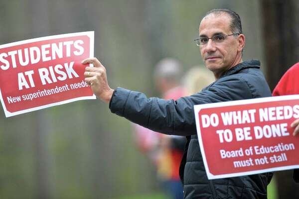 New Fairfield parent Jim Gasparino stands with teachers along the road in front of Meeting House Hill School before the New Fairfield Board of Education meeting on Thursday night. Teachers and the public attending the meeting expressed what they feel is a lack of respect and communication from the board and Superintendent of Schools Alicia Roy.  May 5, 2016, in New Fairfield, Conn.