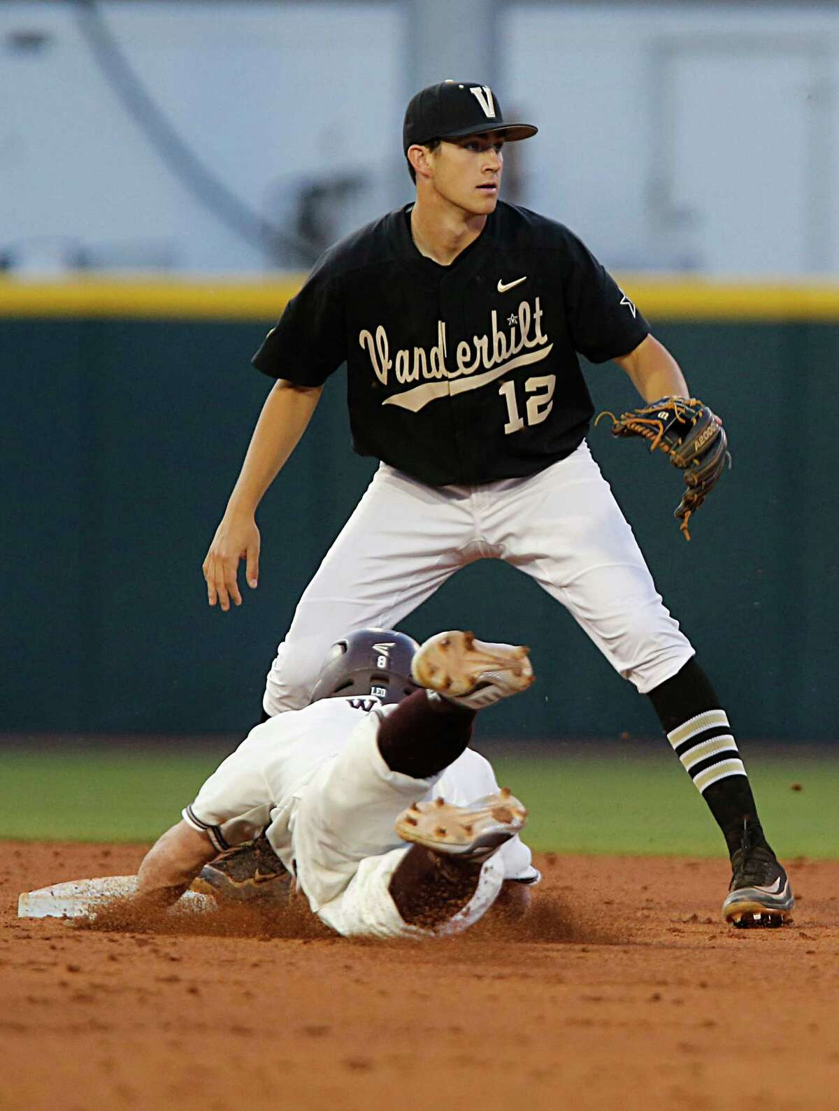 Texas A&M catcher Boomer White left, dives past Vanderbilt infielder Connor Kaiser right, into second base after hitting a double during the sixth inning of college baseball game action at Blue Bell Park Thursday, May 5, 2016, in College Station.
