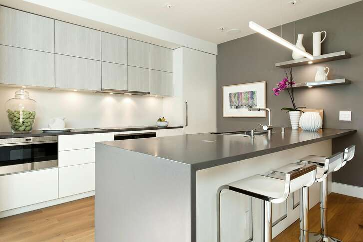 The sleek, German kitchen offers Miele appliances, contemporary lighting, and handleless cabinetry.