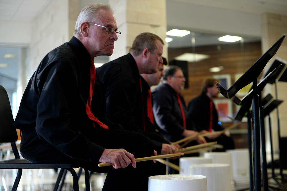 """Percussionists perform on plastic buckets during the Symphony of Southeast Texas' """"Symphony on the Town"""" concert in the Edison Plaza lobby on Thursday evening. The event was held to bring the symphony out of the concert hall and to perform music not typically heard from orchestras.  Photo taken Thursday 5/5/16 Ryan Pelham/The Enterprise Photo: Ryan Pelham / ©2016 The Beaumont Enterprise/Ryan Pelham"""