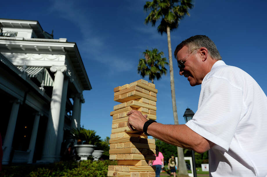 Mike Getz gingerly removes a block while playing Jenga during the spring picnic on the lawn of the McFaddin-Ward House on Thursday evening.  Photo taken Thursday 5/5/16 Ryan Pelham/The Enterprise Photo: Ryan Pelham / ©2016 The Beaumont Enterprise/Ryan Pelham