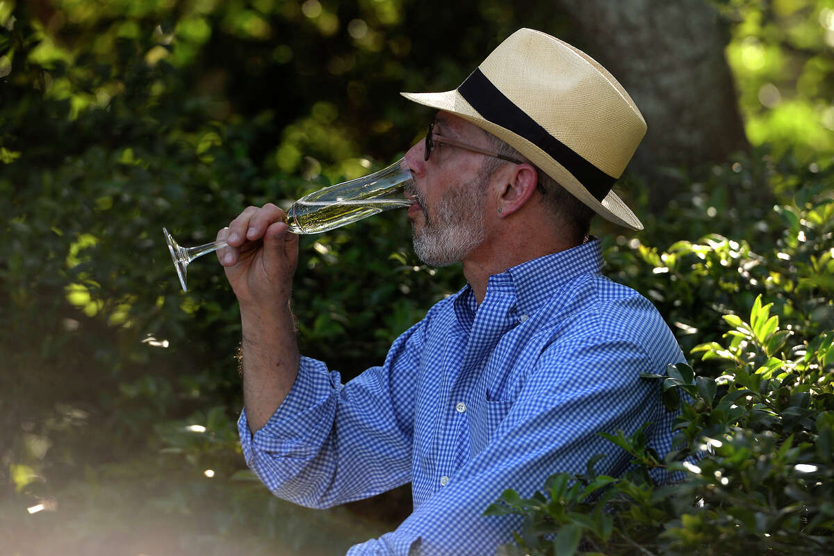 Carlo Busceme takes a sip of his champagne during the spring picnic on the lawn of the McFaddin-Ward House on Thursday evening. Photo taken Thursday 5/5/16 Ryan Pelham/The Enterprise