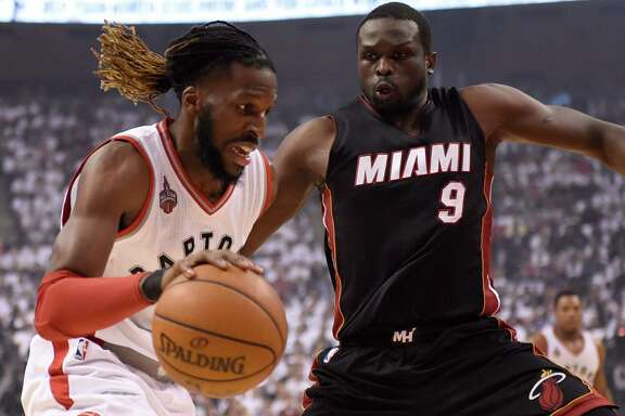 The Raptors' DeMarre Carroll, left, looks for a way around the defense of the Heat's Luol Deng, right. Carroll had 21 points in the Raptors' Game 2 win.