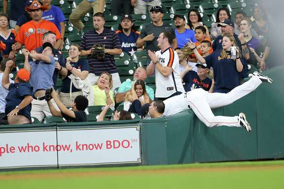 Astros left fielder Jake Marisnick topples over the railing trying to reach a foul ball in the fifth inning Thursday night at Minute Maid Park.