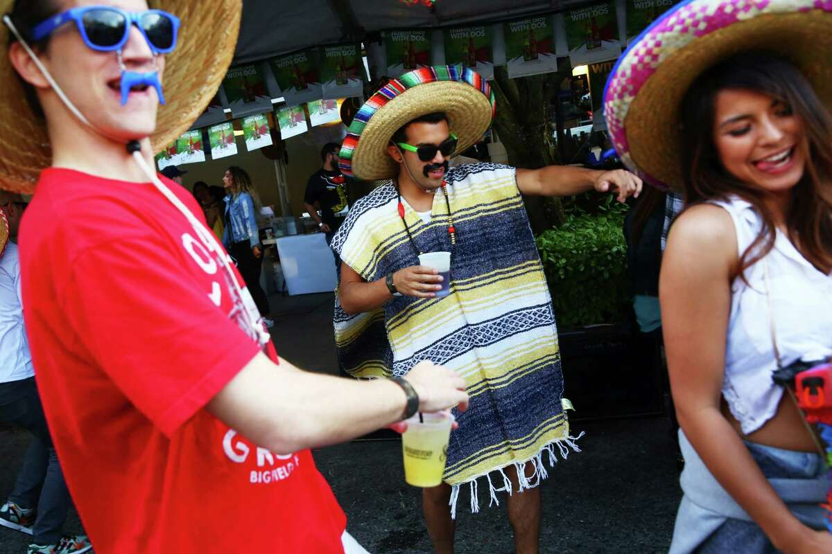 Rich Goodloe, left, Kenzo Kressbach, center, and Samantha Lee dance at the annual Cinco de Mayo block party hosted by the Green Lake Tacos Guaymas, May 5, 2016. The party featured food, drinks, and various djs, bands and dance performances.