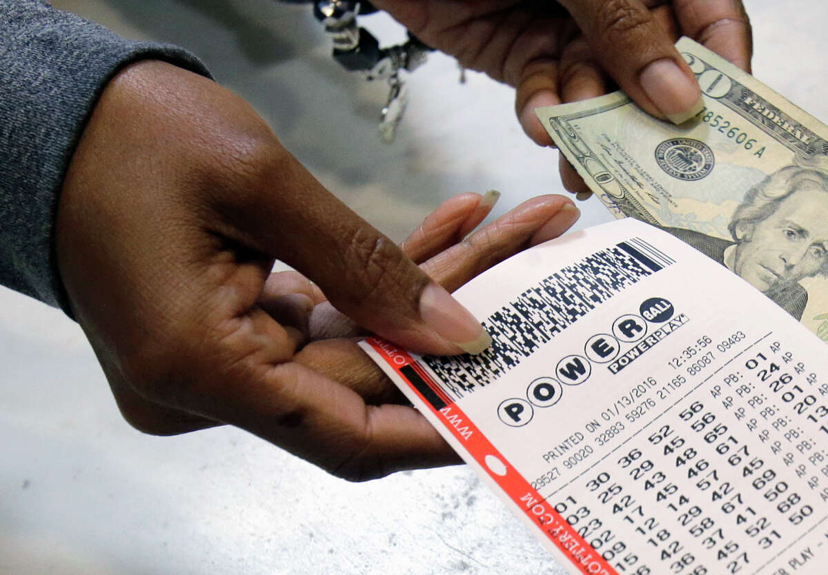In this Jan. 13, 2016 file photo, a clerk hands over a Powerball ticket for cash at Tower City Lottery Stop in Cleveland. Powerball estimates that its jackpot for the May 4, 2016, drawing is $348 million. (AP Photo/Tony Dejak, File)