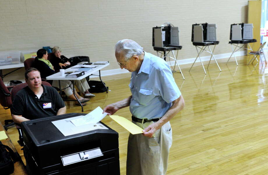 Bernie Lichtenstein casts his ballot at the Bethel Municipal Center, Sept. 16, 2015. Left is Chris Nazro, a tabulator tender. Photo: Carol Kaliff / File Photo / The News-Times