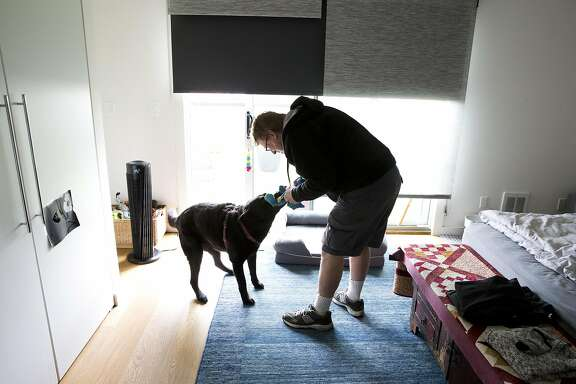 John Clarke, 59, plays with Truffle, one of his regular clients on Wednesday, May 4, 2016 in San Francisco, Calif. Clarke, who is a long-term HIV survivor, has been a dog walker and pet caretaker for the past 15 years.
