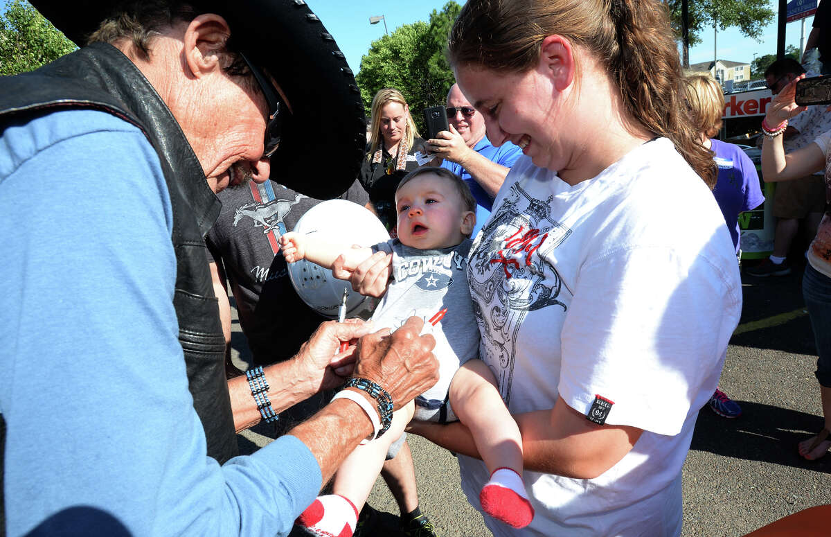 Rachel Nelson holds Hayden Nelson, 7 months, while Richard Petty signs his onesie in Beaumont on Thursday. Petty rode his motorcycle into Beaumont Thursday as part of the Kyle Petty Charity Ride Across America. The event raises money for Victory Junction. Photo taken Thursday, May 05, 2016 Guiseppe Barranco/The Enterprise