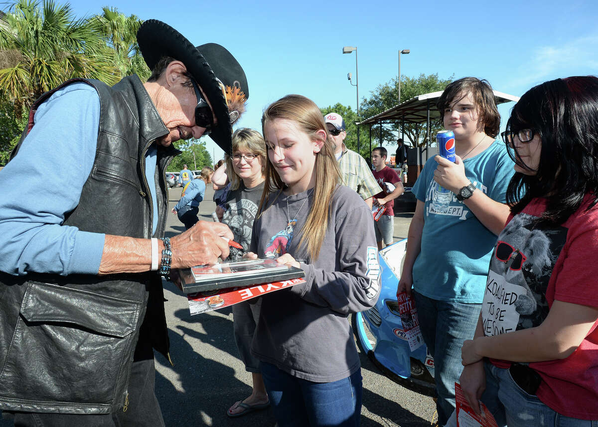 Richard Petty gives Kaylee Golson an autograph in Beaumont on Thursday. Petty rode his motorcycle into Beaumont Thursday as part of the Kyle Petty Charity Ride Across America. The event raises money for Victory Junction. Photo taken Thursday, May 05, 2016 Guiseppe Barranco/The Enterprise