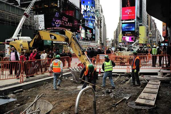 Workers dig to clear cement and soil to rebuild a footpath at the Times Square on Thursday in New York. The 0.3 percentage point rise in average hourly earnings was the most positive sign of the economy's trajectory in Friday's report.