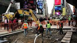 Workers dig to clear cement and soil to rebuild a footpath at the Times Square on Thursday in New York. A hopeful sign of the economy's trajectory in Friday's report was the 0.3 percentage point rise in average hourly earnings.
