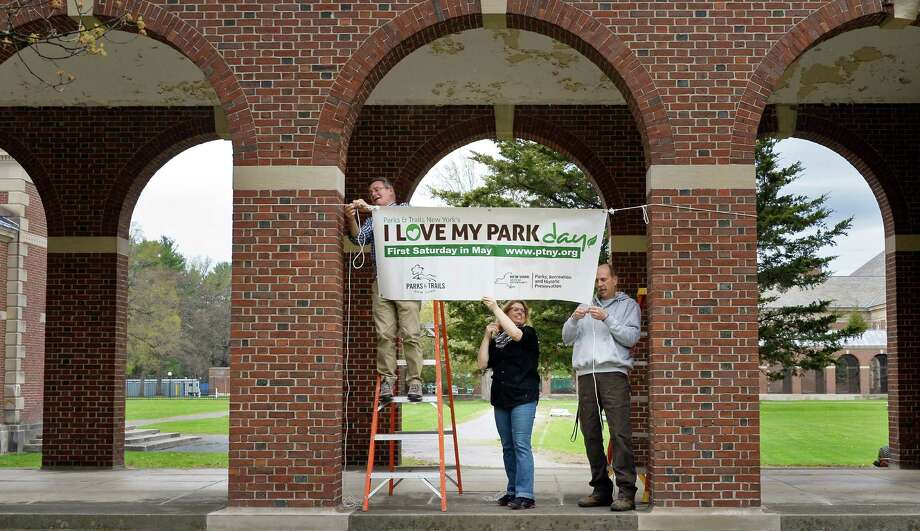 Park staffers Mike Greenslade, left, Jennifer Emmons and Jeff McGreevey, right, hang a banner for Saturday's I Love My Park Days at Saratoga Spa State Park Friday May 6, 2016 in Saratoga Springs, NY. I Love My Park Day is a statewide event to improve and enhance New York's parks and historic sites and bring visibility to the entire park system and its needs.  (John Carl D'Annibale / Times Union) Photo: John Carl D'Annibale