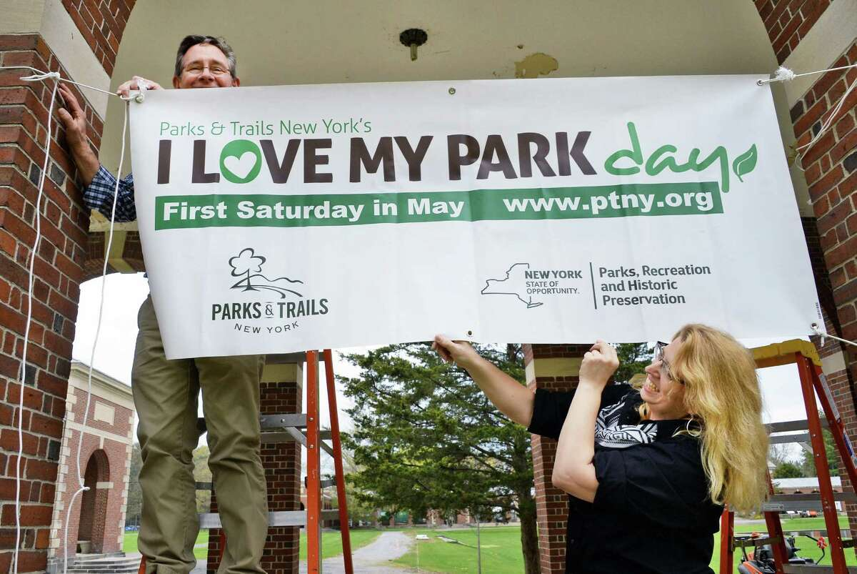 Park staffers Mike Greenslade, left, and Jennifer Emmons hang a banner for Saturday's I Love My Park Days at Saratoga Spa State Park Friday May 6, 2016 in Saratoga Springs, NY. I Love My Park Day is a statewide event to improve and enhance New York's parks and historic sites and bring visibility to the entire park system and its needs. (John Carl D'Annibale / Times Union)