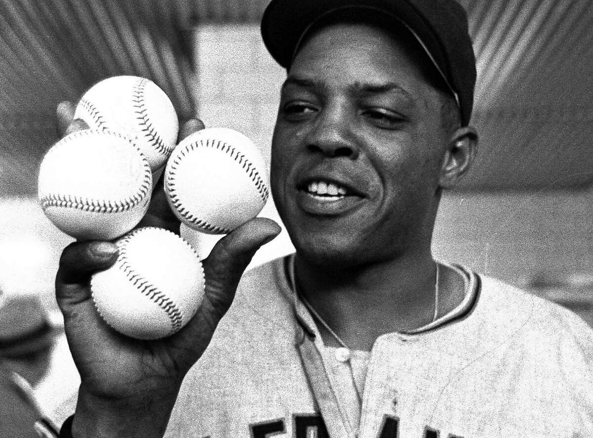 In this Aptil 30, 1961, file photo, San Francisco Giants star outfielder, Willie Mays, proudly displays the four baseballs in the clubhouse representing the four homers which he hit against the Milwaukee Braves in Milwaukee. The four homers tied the record of four homers in a single game held by nine other major league players at the time. The Giants won 14-4. Willie's homers accounted for eight runs batted in.(AP Photo/File)