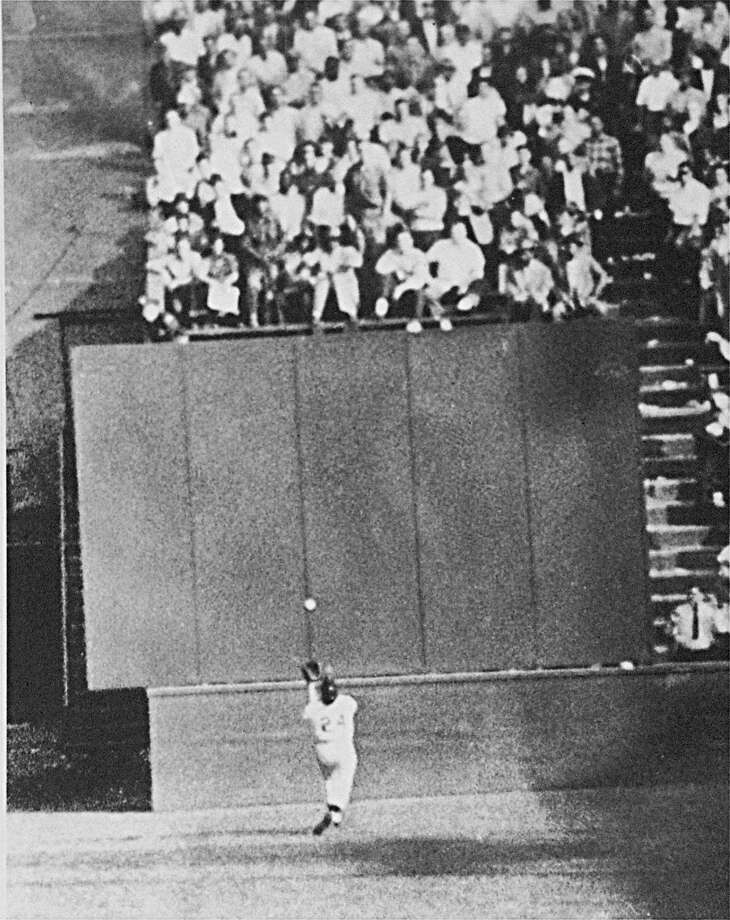 Running at top speed with his back to the plate, New York Giant center fielder Willie Mays gets under a 450-foot blast off the bat of Cleveland first baseman Vic Wertz to pull the ball down in front of the bleachers wall in the eighth inning of the World Series opener at the Polo Grounds in New York on September 29, 1954. In making the miraculous catch with two runners on base, Willie came within a step of crashing into the wall. Photo: AP