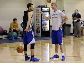 Golden State Warriors' Stephen Curry, left, speaks with player development coach Bruce Fraser during NBA basketball practice on Thursday, May 5, 2016, in Oakland, Calif. Golden State will face the Portland Trail Blazers in Game 3 of a second-round NBA basketball playoff series on Saturday, May 7 in Portland. (AP Photo/Ben Margot)