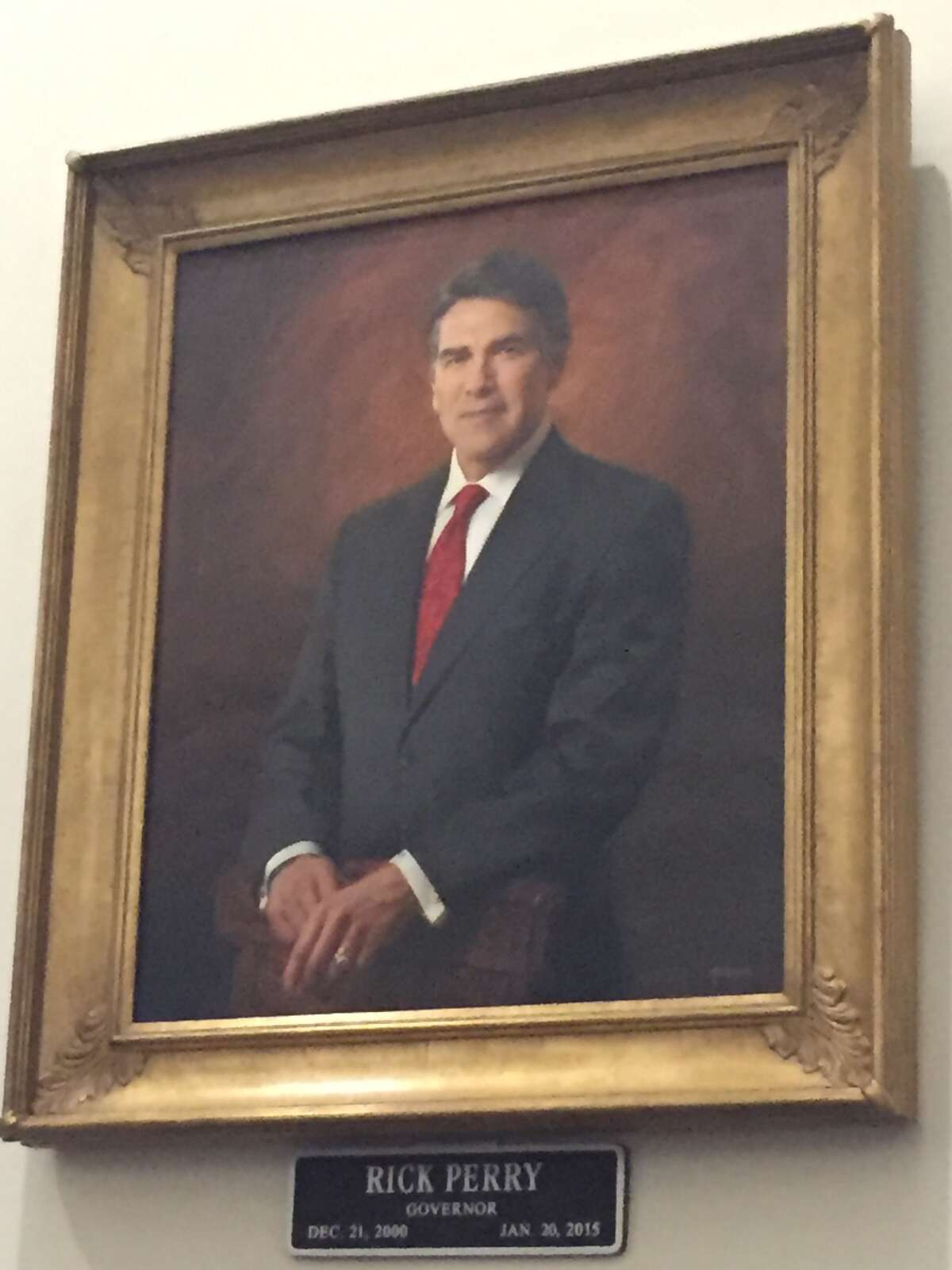 Rick Perry's official state portrait was unveiled Friday, May 6, 2016, in Austin, but another likeness of the former Texas governor took the Internet by storm in 2014 when he was booked into the Travis County Jail.
