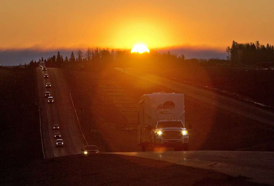 Evacuees leave Fort McMurray in the early morning, after being stranded north of wildfire Photo: JASON FRANSON, Associated Press