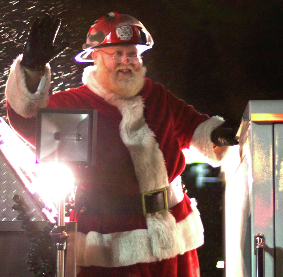 Santa Claus, aka New Milford firefighter Bill Buckbee, arrives aboard a Water Witch Hose Co. No. 2 fire truck for the New Milford Commission on the Arts' annual carol sing, on Dec. 17, 2012, on the Village Green. Photo: File Photo / Trish Haldin