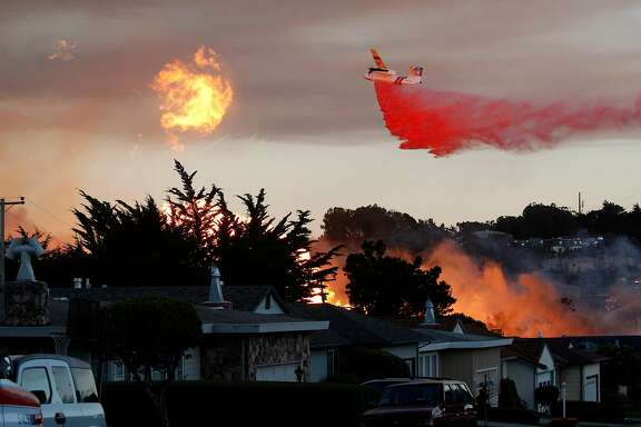 """FILE - In this Sept. 9, 2010, file photo, a massive fire following a pipeline explosion roars through a mostly residential neighborhood in San Bruno, Calif. Repeated natural-gas accidents including a pipeline explosion that killed eight people suggest that Pacific Gas & Electric Co., California's largest power utility, may be too big to operate safely, the state's top utility regulator says. California Public Utilities Commission President Michael Picker said he would ask the commission's staff to study """"the culture of safety"""" and the structure of the utility, which he noted currently has its gas and electricity operations under a single board and CEO. PG&E is one of the country's largest power utilities with 9.7 million gas and electric customers. The Associated Press obtained Picker's prepared statement ahead of a commission meeting Thursday, April 9, 2015, where the panel is expected to vote on a record $1.6 billion penalty for the 2010 PG&E gas pipeline explosion in a San Francisco suburb.  (AP Photo/Jeff Chiu, File)"""