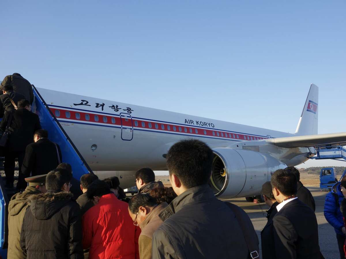 Passengers are boarding on a plane. The Air Koryo plane will depart from Pyongyang to Beijing.